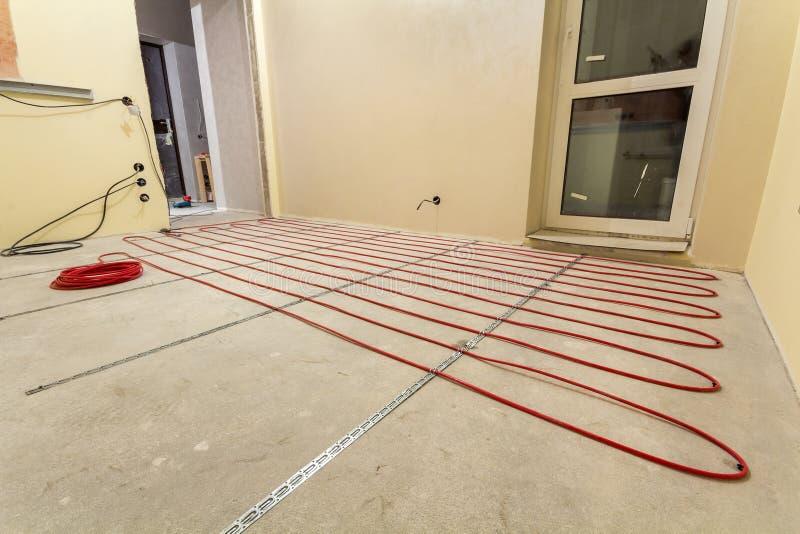 V?rma r?d tr?dinstallation f?r elektrisk kabel p? cementgolv i litet nytt oavslutat rum med packade v?ggar Renovering och arkivfoton