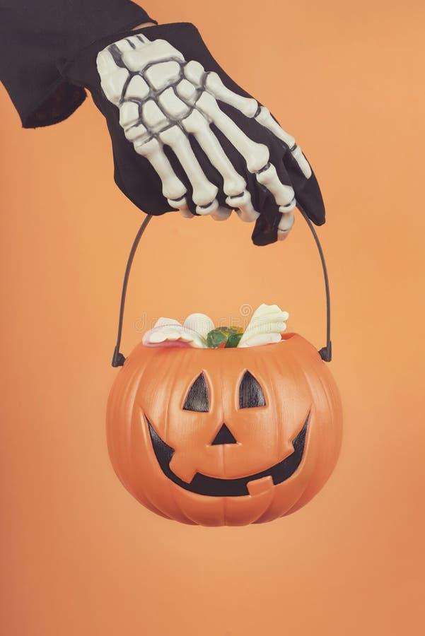 V?spera de Todos los Santos feliz La mano del niño en un guante esquelético con la calabaza de Halloween fotos de archivo libres de regalías