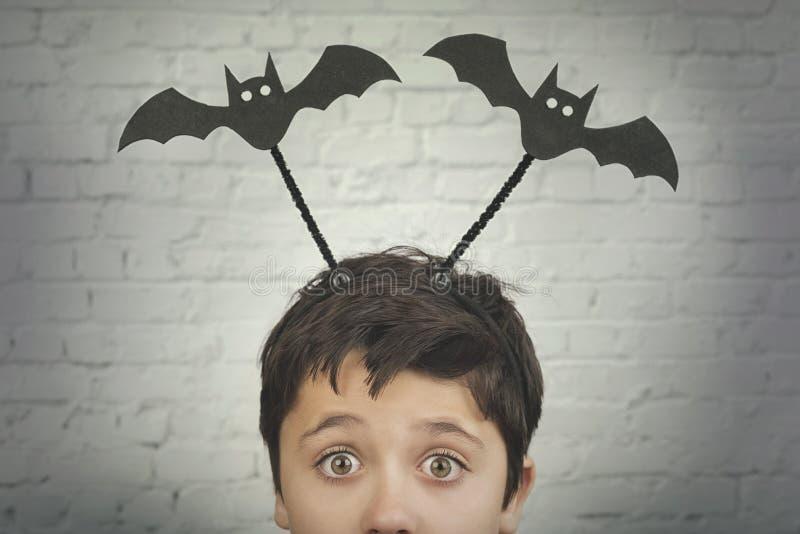 V?spera de Todos los Santos feliz niño divertido con los vampiros de Halloween encima en su cabeza foto de archivo