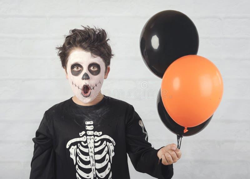 V?spera de Todos los Santos feliz niño divertido en un traje esquelético con los globos coloridos fotografía de archivo
