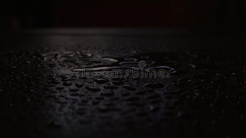 V?t asfalt, nattplats av en tom gata med lite reflexion i vattnet royaltyfri bild