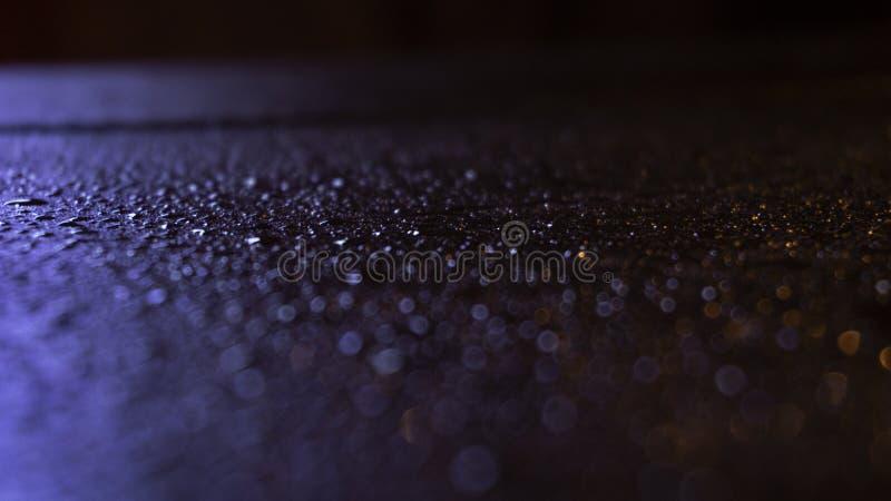 V?t asfalt, nattplats av en tom gata med lite reflexion i vattnet arkivfoto