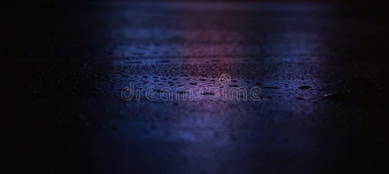 V?t asfalt, nattplats av en tom gata med lite reflexion i vattnet arkivfoton