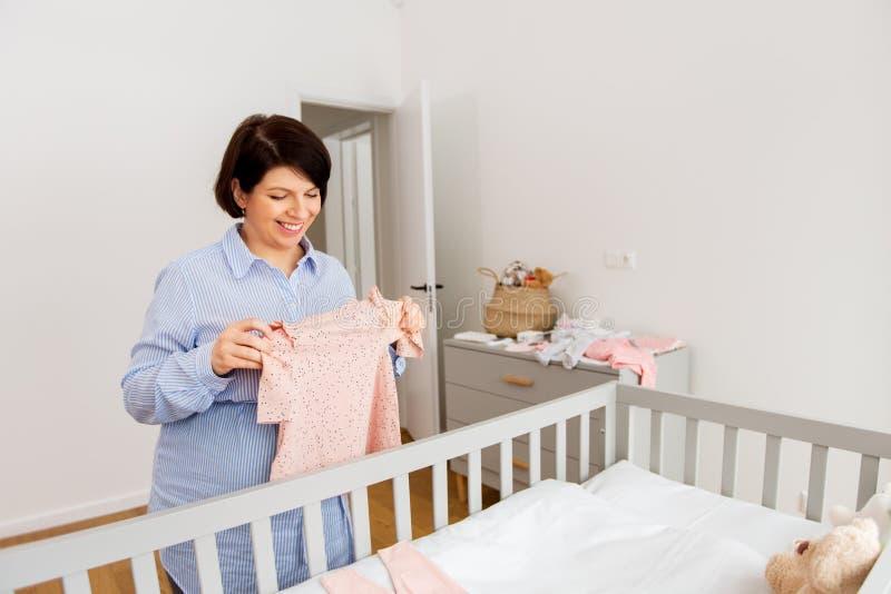 V?tements heureux de b?b? d'arrangement de femme enceinte ? la maison photo stock