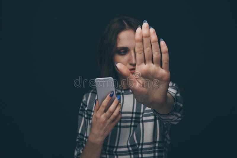 V?tima adolescente triste ser do cyber que tiraniza o assento em linha em um sof? na sala de visitas em foto de stock royalty free