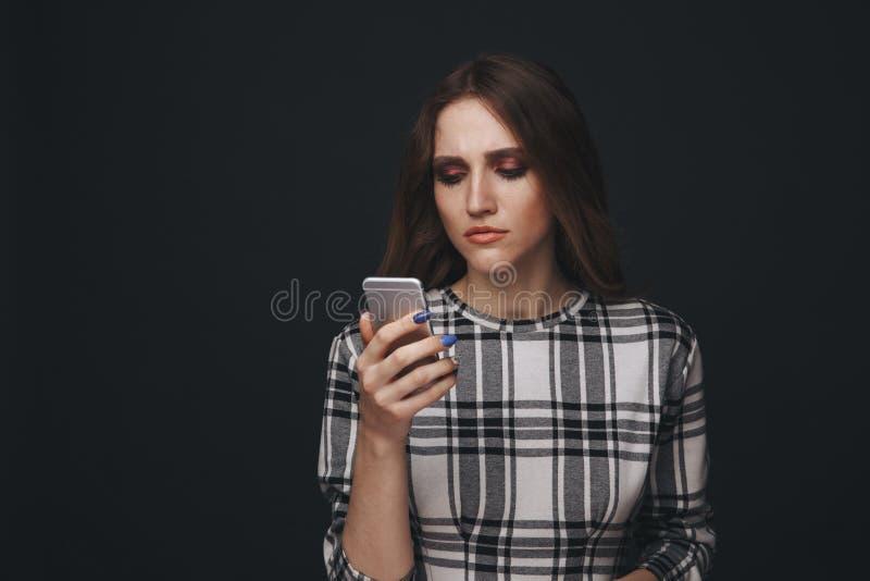 V?tima adolescente triste ser do cyber que tiraniza o assento em linha em um sof? na sala de visitas em imagens de stock