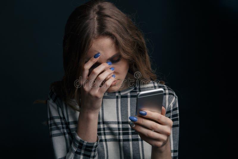 V?tima adolescente triste ser do cyber que tiraniza o assento em linha em um sof? na sala de visitas em fotos de stock royalty free