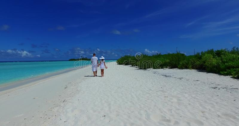 V12622 two 2 people walking romantic young people couple holding hands on a tropical island of white sand beach and blue foto de archivo libre de regalías