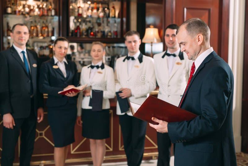 V?xelverkan av personalen Hotell- eller restaurangchef och hans personal i kök växelverkan till huvudkocken in royaltyfri bild