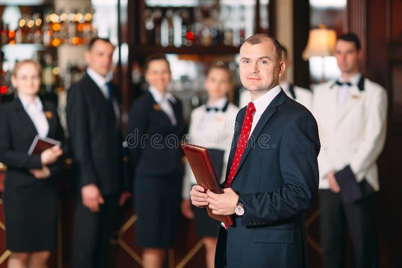 V?xelverkan av personalen Hotell- eller restaurangchef och hans personal i kök växelverkan till huvudkocken in arkivbilder