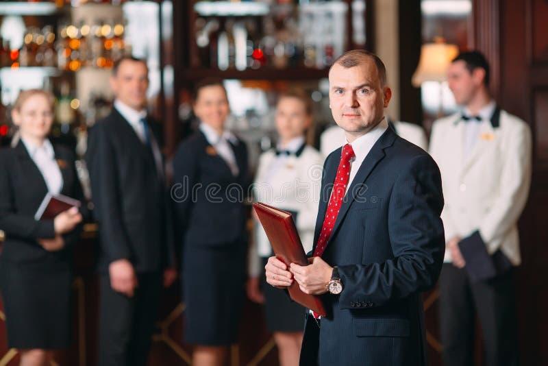 V?xelverkan av personalen Hotell- eller restaurangchef och hans personal i kök växelverkan till huvudkocken in arkivbild