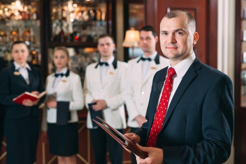 V?xelverkan av personalen Hotell- eller restaurangchef och hans personal i kök växelverkan till huvudkocken in arkivfoto