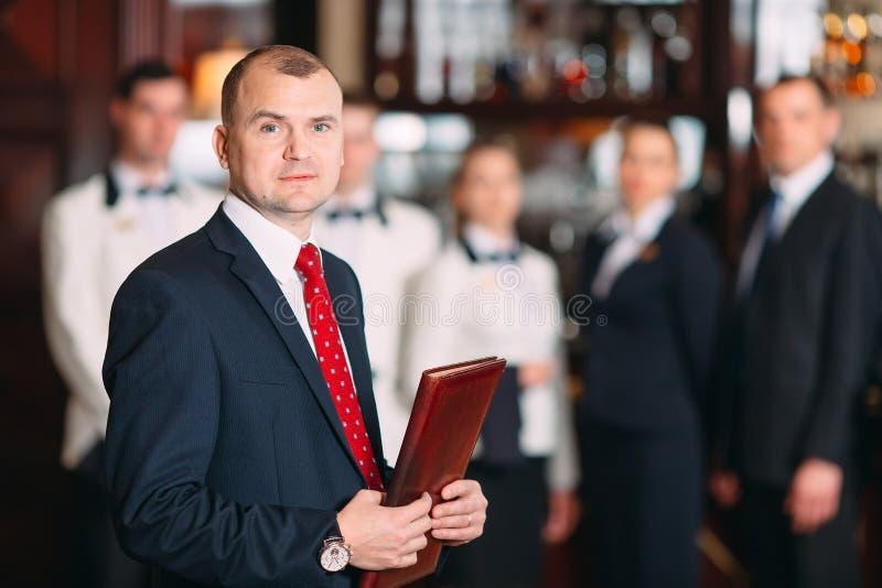 V?xelverkan av personalen Hotell- eller restaurangchef och hans personal i kök växelverkan till huvudkocken in royaltyfri foto