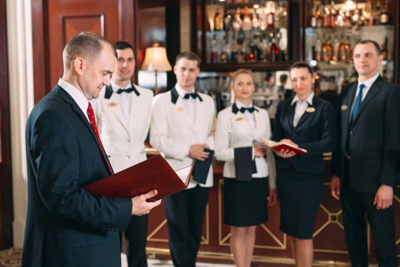 V?xelverkan av personalen Hotell- eller restaurangchef och hans personal i kök växelverkan till huvudkocken in arkivfoton