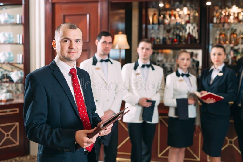 V?xelverkan av personalen Hotell- eller restaurangchef och hans personal i kök växelverkan till huvudkocken in royaltyfri fotografi