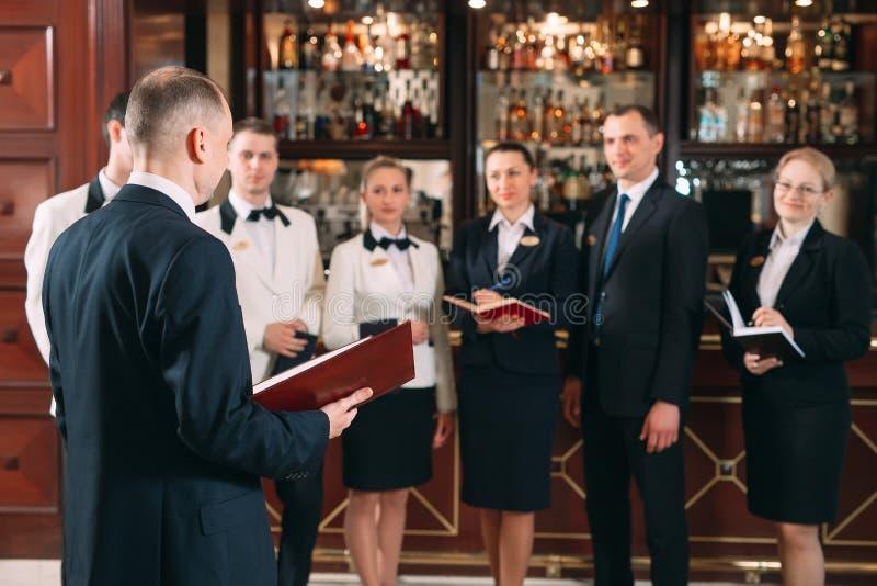 V?xelverkan av personalen Hotell- eller restaurangchef och hans personal i kök växelverkan till huvudkocken in royaltyfria bilder