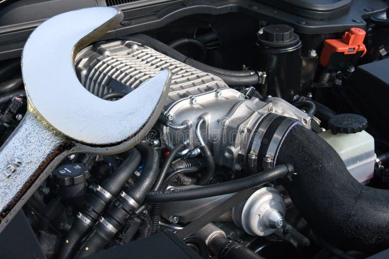 V8 ha sovralimentato il motore e la chiave di automobile fotografia stock