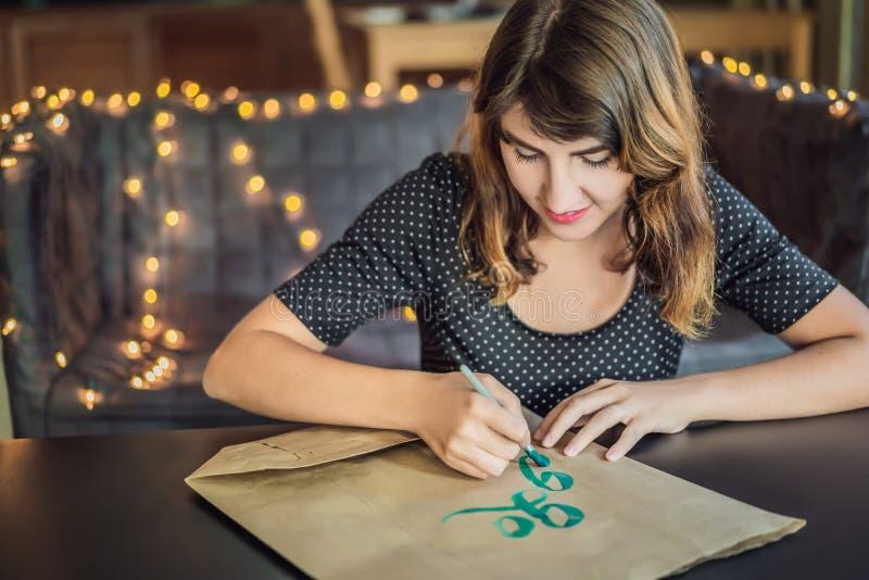 va el verde El cal?grafo Young Woman escribe frase en el Libro Blanco Inscripci?n de letras adornadas ornamentales calligraphy fotografía de archivo libre de regalías