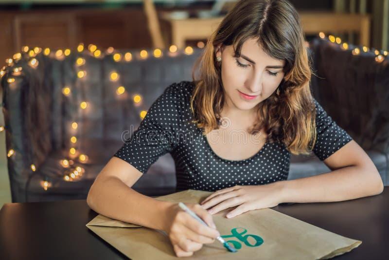 va il verde Il calligrafo Young Woman scrive la frase su Libro Bianco Iscrivendo l'ornamentale ha decorato le lettere calligraphy immagine stock