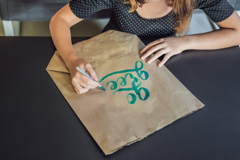 va il verde Il calligrafo Young Woman scrive la frase su Libro Bianco Iscrivendo l'ornamentale ha decorato le lettere calligraphy fotografia stock libera da diritti
