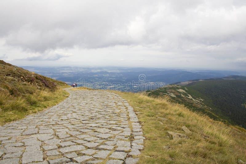 Va la montagna che fa un'escursione in una traccia concreta fotografia stock