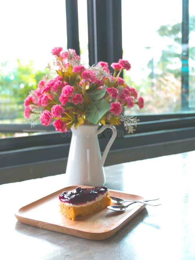Vaag beeld van Roze bloemen in witte vaas en bosbessenpastei royalty-vrije stock foto