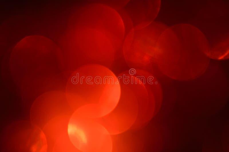 Vaag, bokeh rode lichtenachtergrond. Abstracte fonkelingen