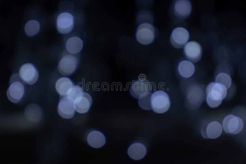 Vaag defocused zilveren, witte en blauwe heldere lichte, glanzende vlekken bokeh achtergrond stock afbeelding