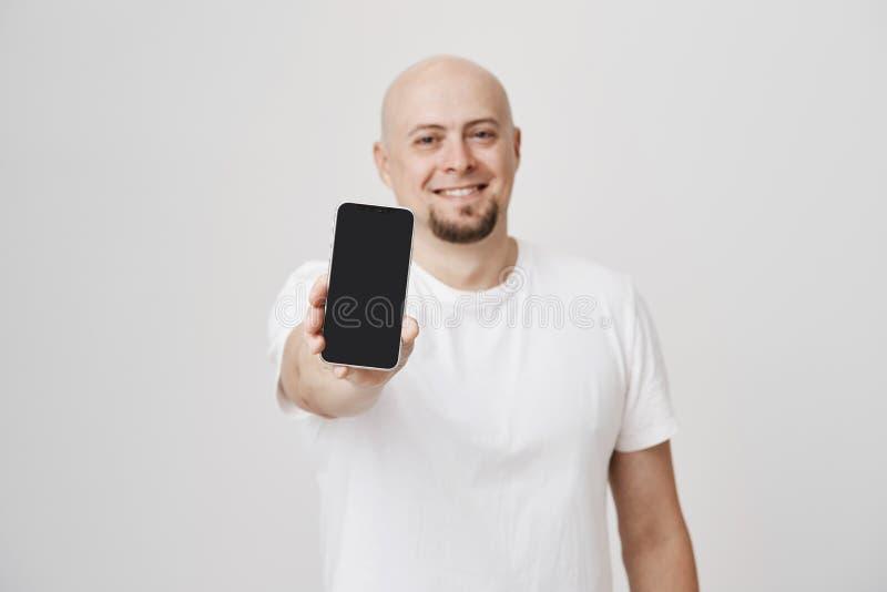 Vaag portret die van aantrekkelijke kale volwassen Kaukasische mannelijke het uitbreiden zich hand met smartphone naar camera, ru royalty-vrije stock foto's