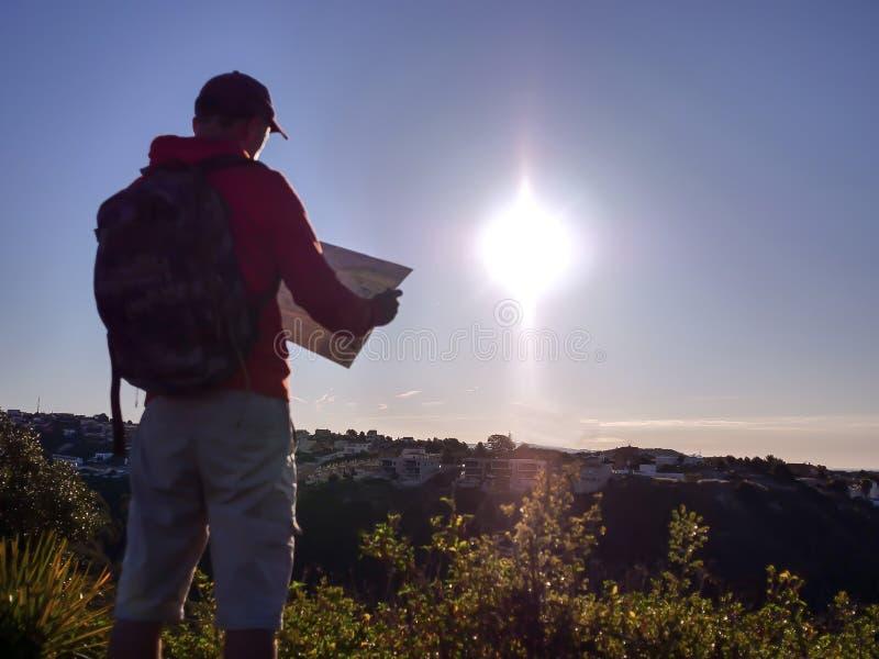 Vaag silhouet van een toeristenkerel met een kaart, op de achtergrond van de stad op een heuvel, bij zonsopgang stock afbeelding