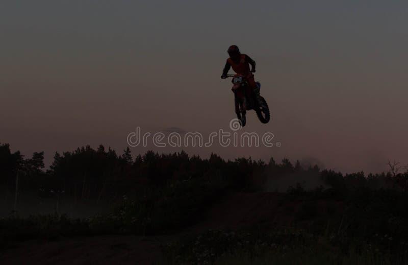 Vaag silhouet van motocrossruiter het springen op de berg in zonsondergang royalty-vrije stock afbeeldingen