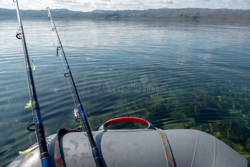 vaartuigen die vissen in de diepblauwe zee met staafjes en hengels royalty-vrije stock afbeelding