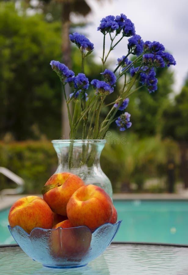 Vaas met bloemen en perziken door de pool stock foto's