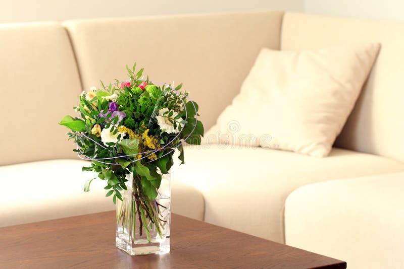 Vaas met bloemen in woonkamer stock afbeelding