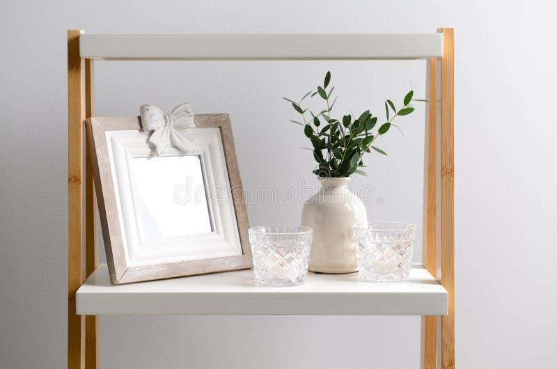 Vaas met eucalyptustakken en de houders van de glaskaars op witte lijst stock foto's