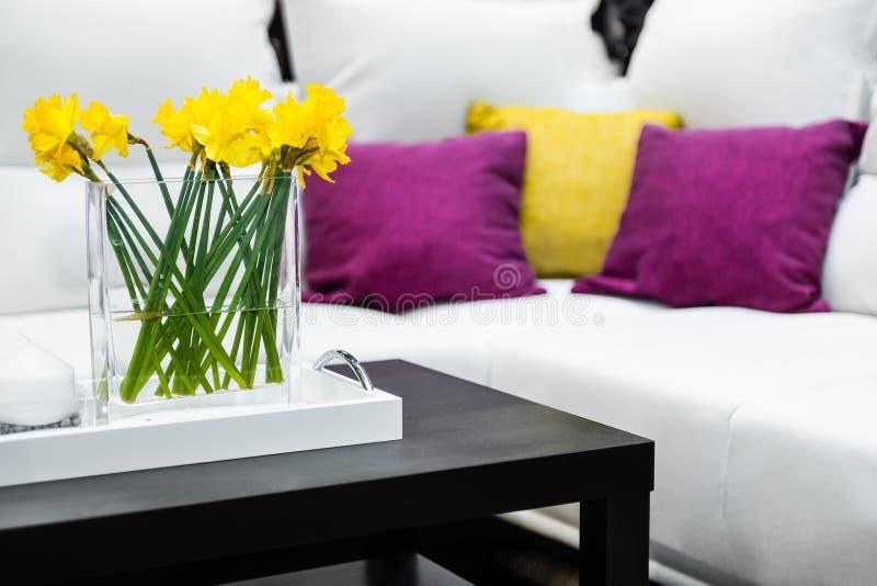 Vaas met gele narcisbloemen voor witte bank stock foto's