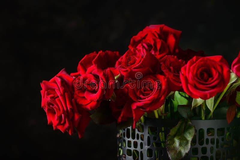 Vaas met mooi boeket van rode rozen op donkere achtergrond royalty-vrije stock afbeeldingen