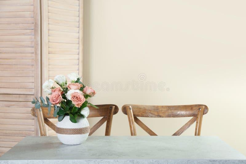 Vaas met mooie bloemen als element van binnenlands ontwerp op lijst in ruimte royalty-vrije stock fotografie