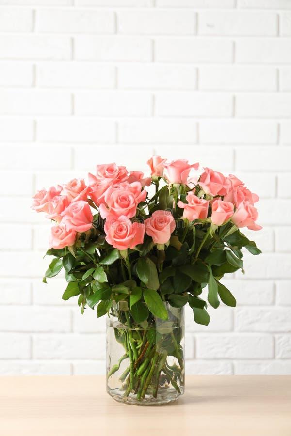 Vaas met mooie roze bloemen op lijst stock foto