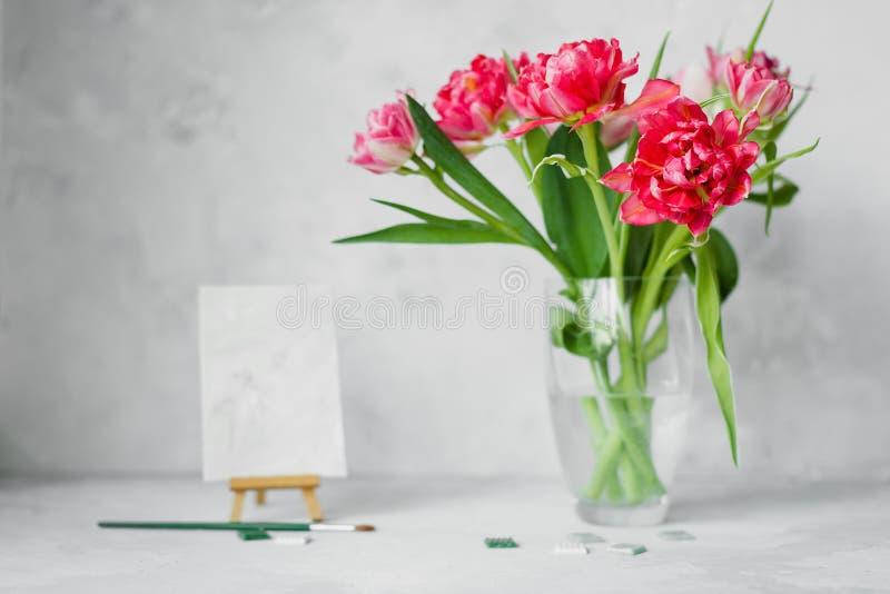 Vaas met tulpenbloemen, penseel met kleur op canvas het schilderen en mozaïek op grijze backround royalty-vrije stock foto
