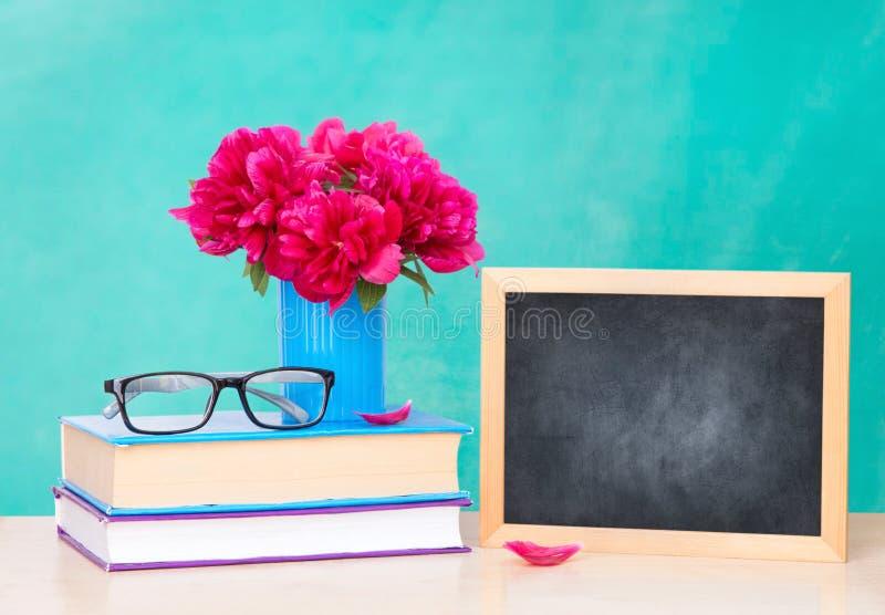 Vaas op een stapel van boeken en een houten kader voor het schrijven op een lijst, de dag van kennis stock afbeelding