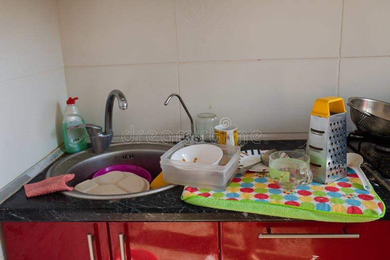 Vaatwerk en dishware het drogen op handdoek De schone schotels en keukengerei het drogen op een kleurrijke handdoek dichtbij de k stock foto