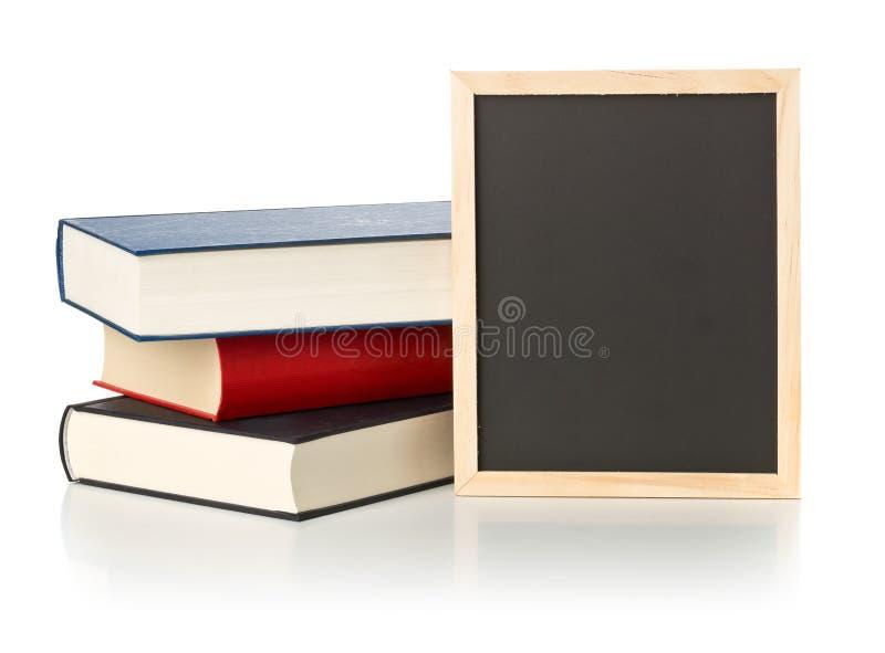 Vacío, espacio en blanco, pizarra negra con la pila de libros sobre blanco imágenes de archivo libres de regalías