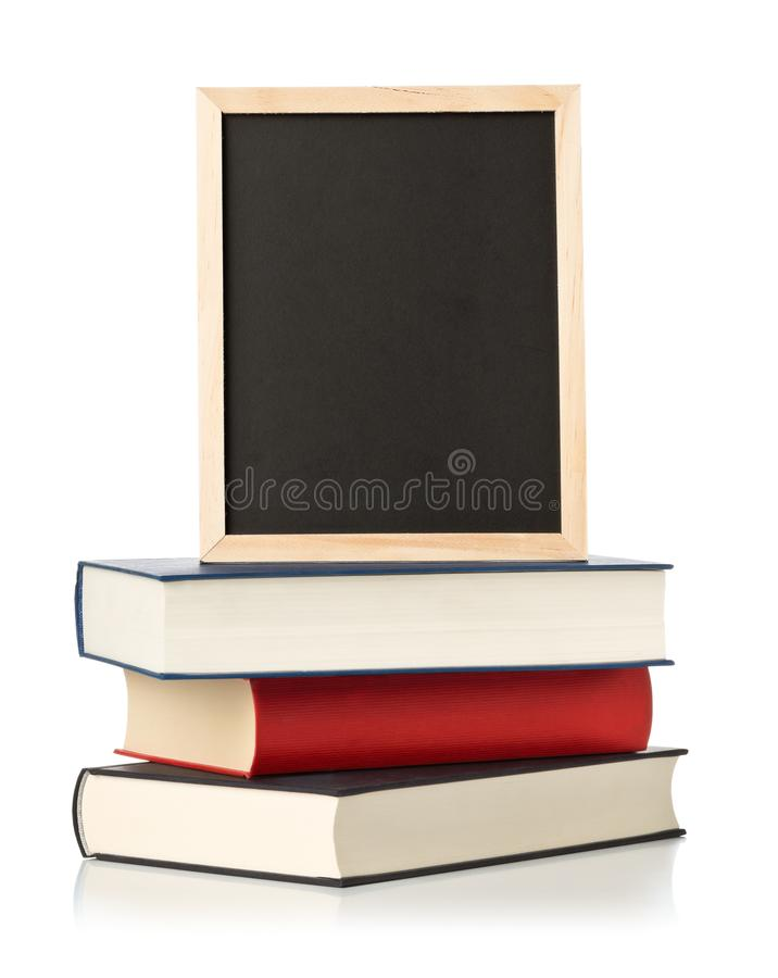 Vacío, espacio en blanco, pizarra negra con la pila de libros sobre blanco foto de archivo