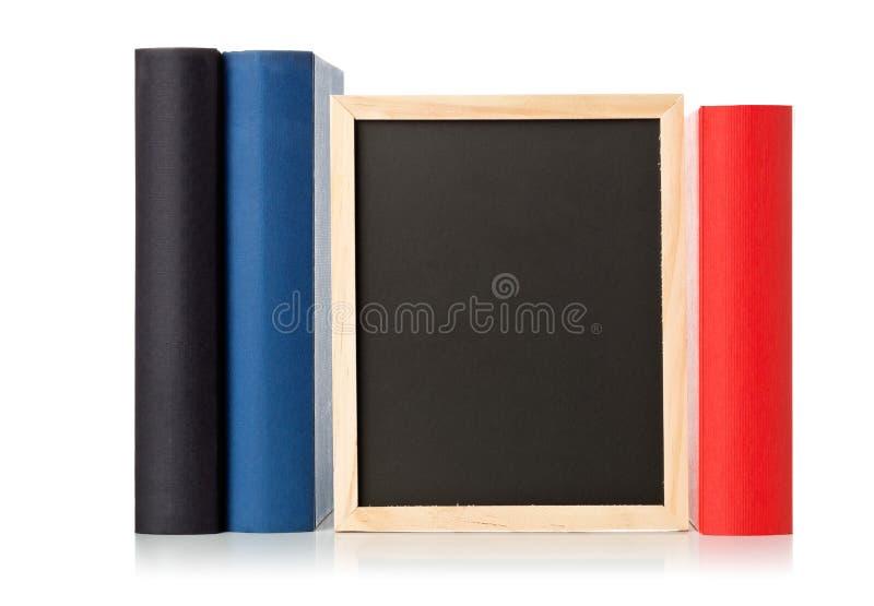 Vacío, espacio en blanco, pizarra negra entre los libros sobre blanco fotos de archivo libres de regalías