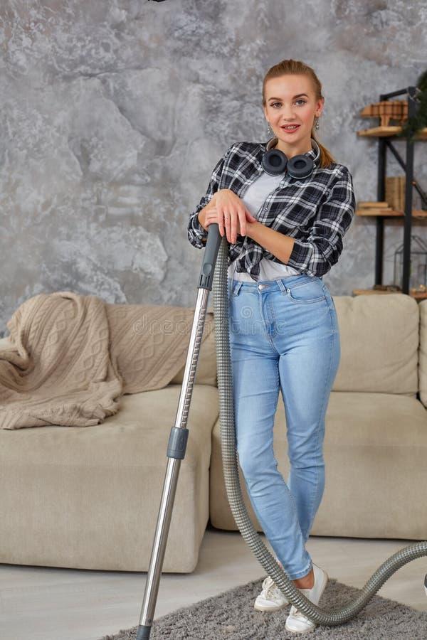 Vacío sonriente joven de la mujer que limpia la alfombra en la sala de estar, interior escandinavo moderno A casa, economía domés foto de archivo