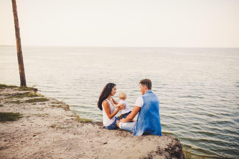 Vacaciones de familia del tema con el pequeño niño en la naturaleza y el mar La mamá, el papá y la hija de un año se están sentan imagen de archivo