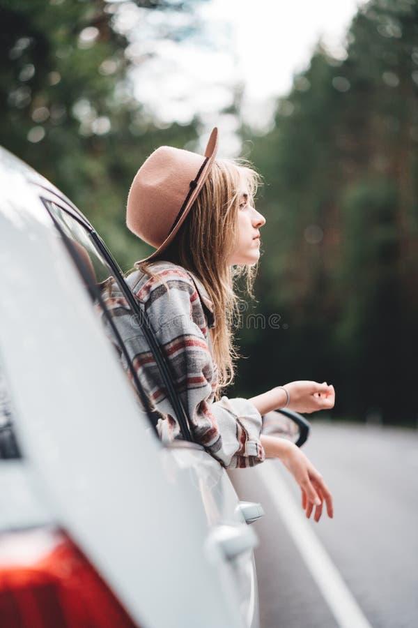 Vacaciones de la aventura de la muchacha feliz del inconformista que viajan Mujer de Boho que se sienta en el coche que mira de v fotografía de archivo