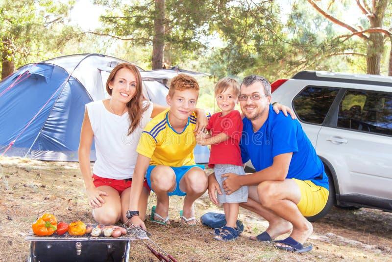Vacaciones de la barbacoa de la familia La familia feliz tiene comida campestre (el Bbq) imagenes de archivo