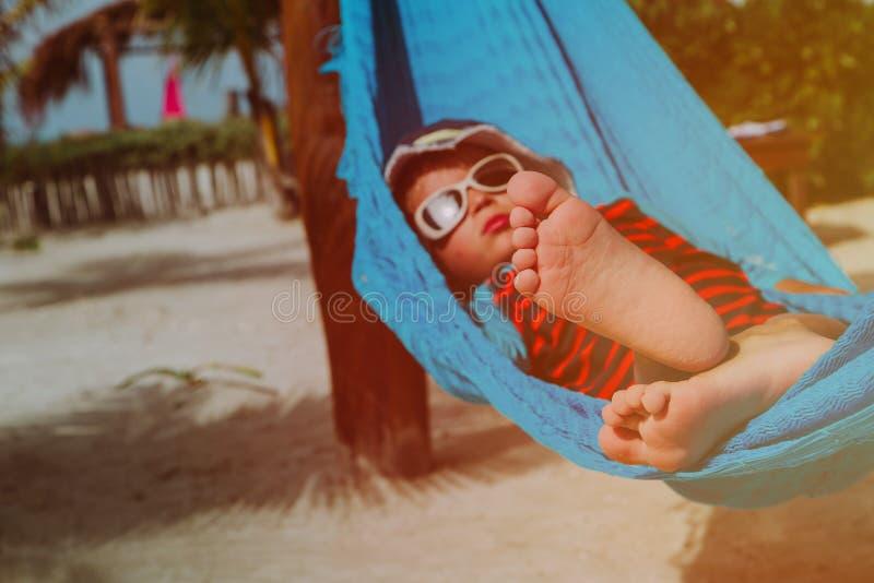 Vacaciones de la playa - niño pequeño feliz relajado en hamaca en el mar fotos de archivo
